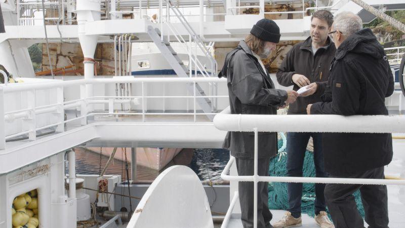 Regissør Petter Misje instruerer skuespillerne Mike McGurk fra Bømlo (t.v) og John McMillan fra Stord (t.h) under innspillingen i Austevoll.