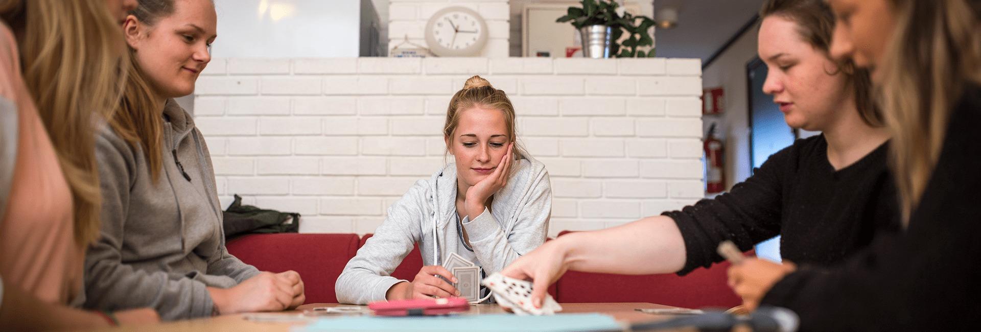 En venninnegjeng på Bømlo Folkehøgskule spiller kort i stua.