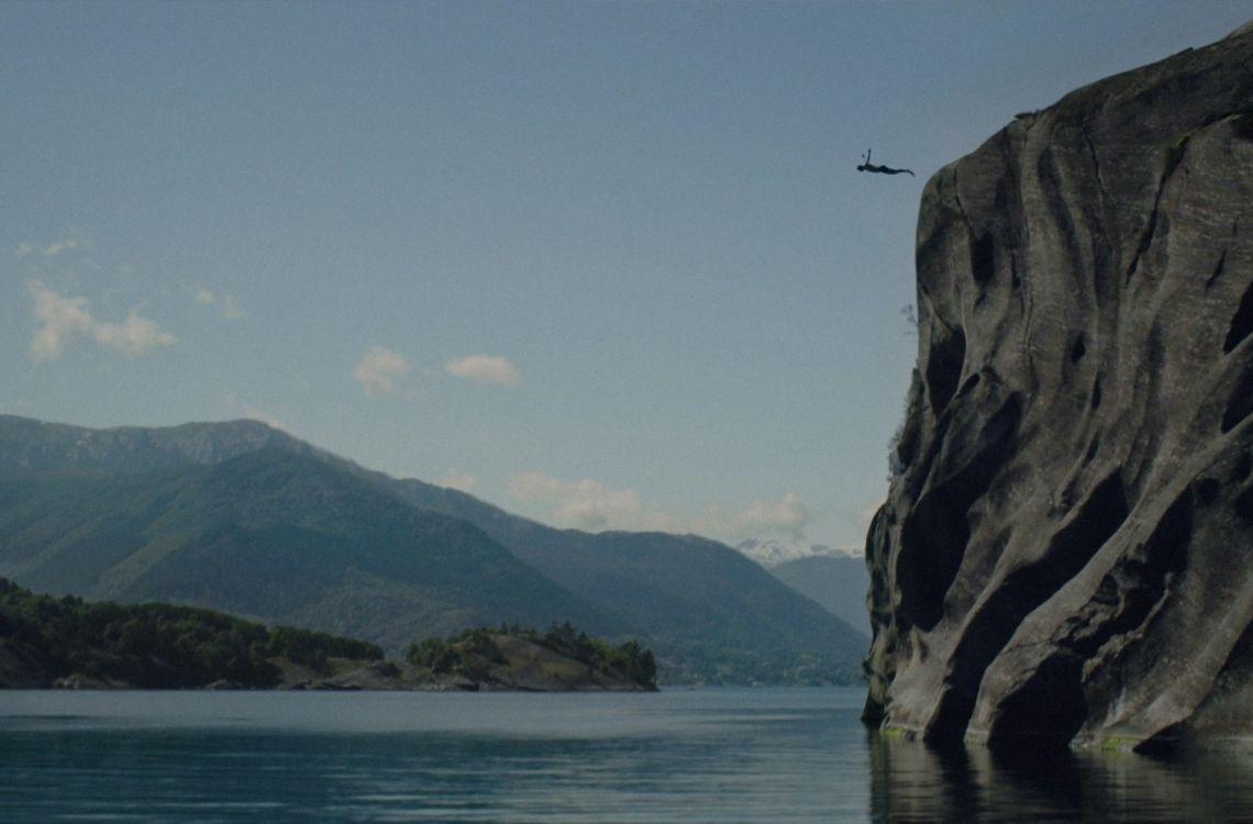 En mann stuper fra et høyt fjell mot shøen. Fjordlandskap i bakgrunnen