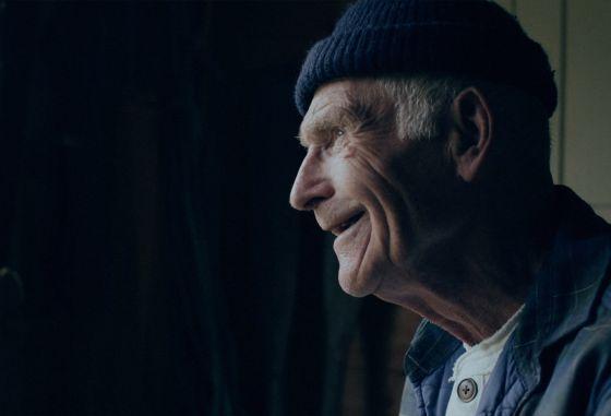 En eldre mann ser smilende ut vinduet