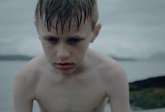 En våt gutt etter etmislykket stup ser trist på vannet.