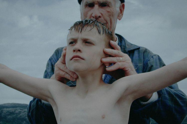 En mann instruerer en gutt før et stup. Armene rett ut og hodet høyt hevet.
