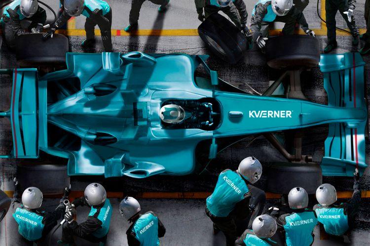 En turkis formel1-bil sett ovenfra med Kværner-logo på panseret. Bilen er inne i pitstop'en og får overhaling av teamet.