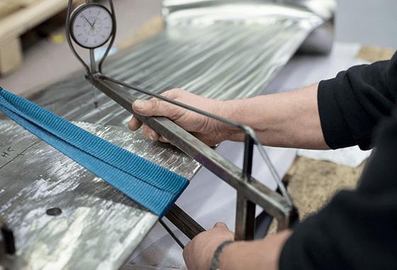Servogear-ansatt som arbeider med metall og måleinstrument.
